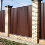 Забор из профлиста на ленте с кирпичными столбами. Цвет шоколад